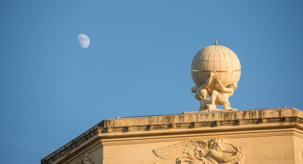 The moon is seen against the globe at the top of the Radcliffe Observatory at sunset