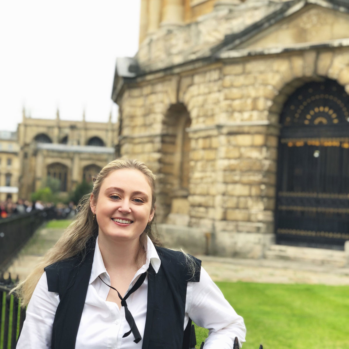 Emily Gough in sub fusc on matriculation day standing outside the Radcliffe Camera