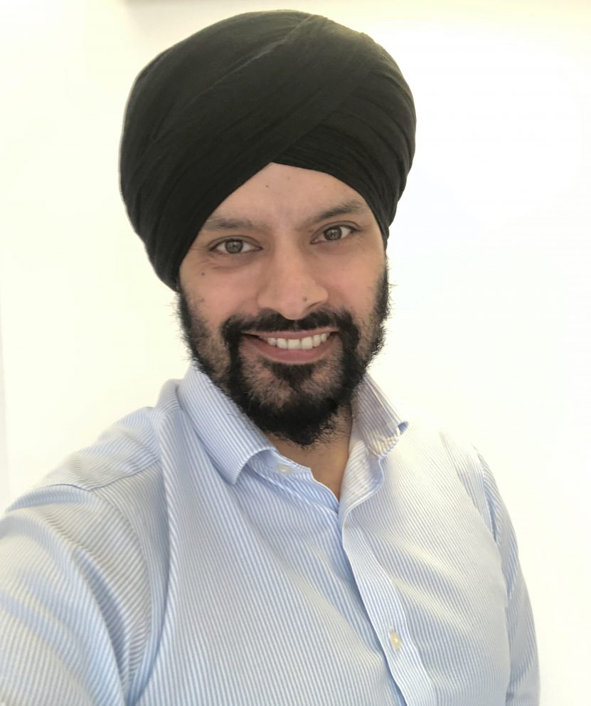 Gurdeep Mannu wears a blue striped shirt and smiles as he takes a selfie
