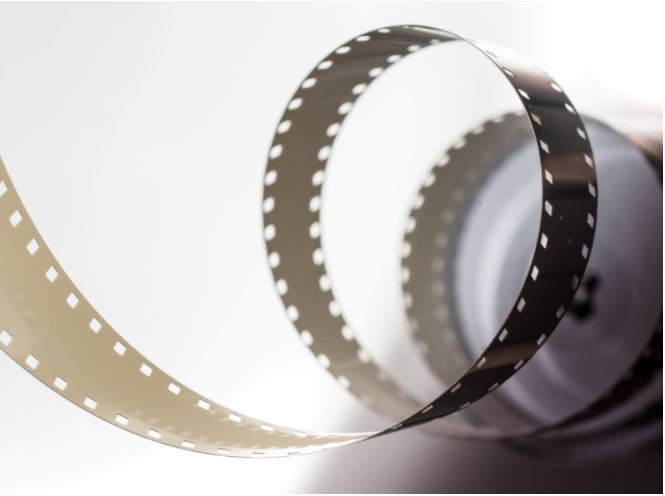 An old reel of movie film springing out from a tight curl