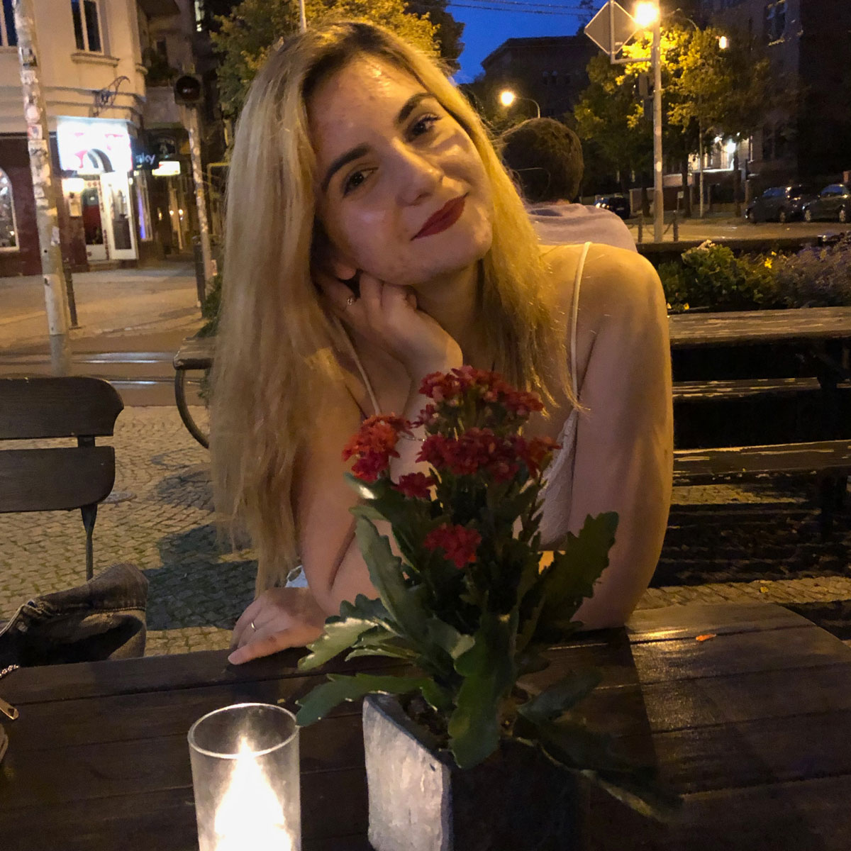 Sofija Paneva at an outdoor restaurant table at nighttime with a flickering candle in front of her