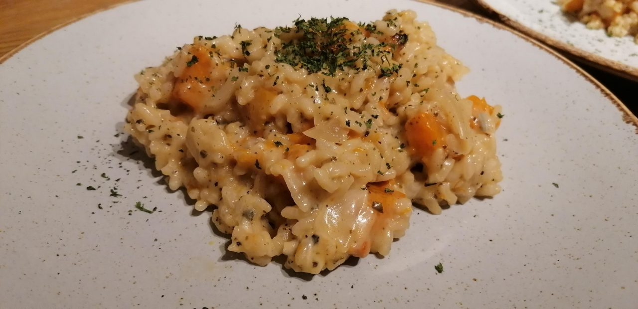 Fluffy, creamy and delicious roast butternut squash risotto with a sage garnish on a white plate