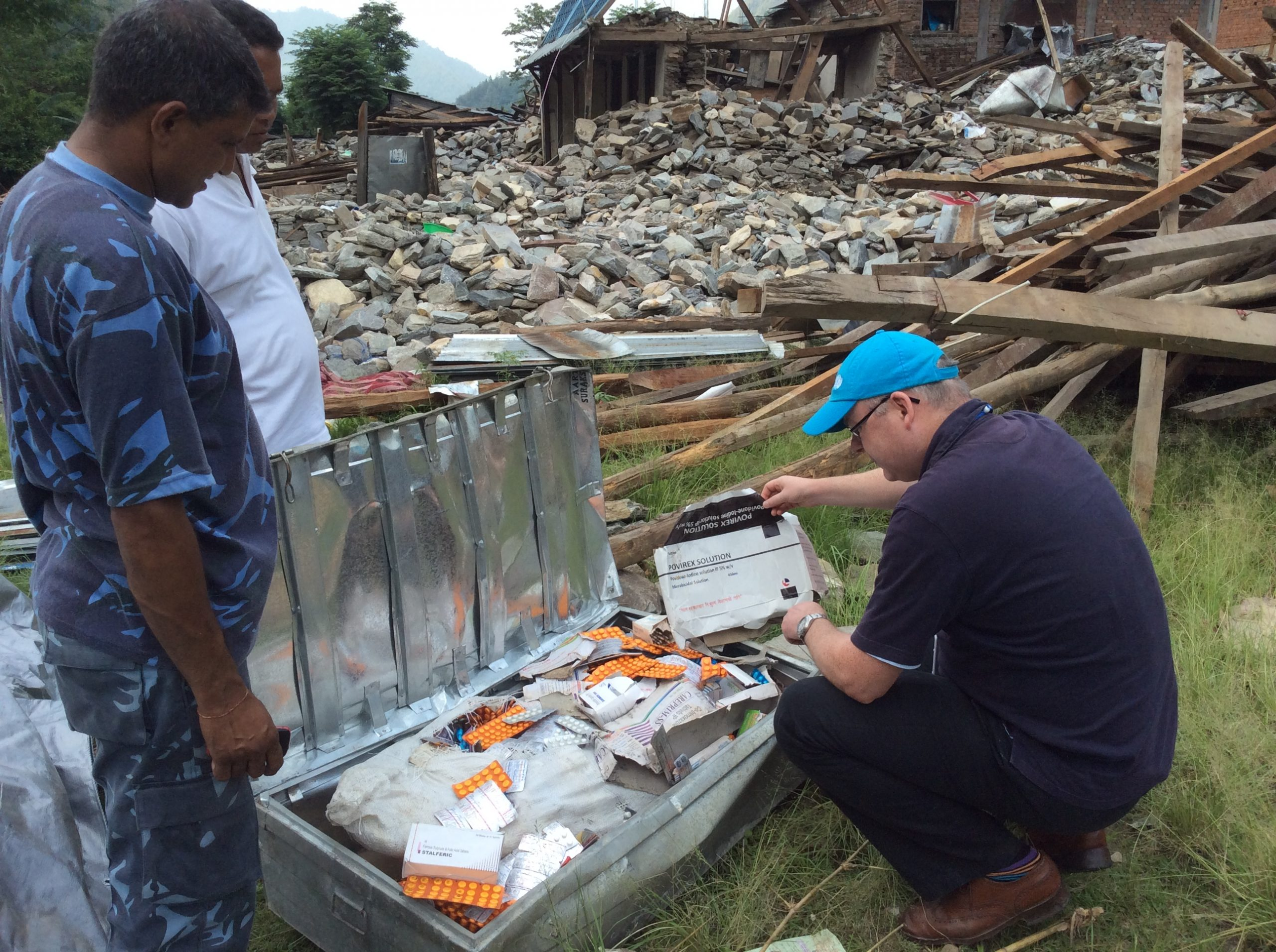 Douglas Noble examining a box of rescue supplies while surrounded by debris from the 2015 earthquake in Nepal