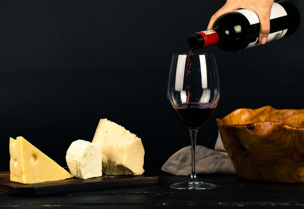 A woman with pink nail varnish pours a bottle of deep red wine into a tall wine glass that sits on a table surrounded by different cheeses