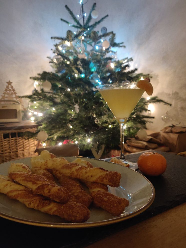 A martini glass of orange liquid and a plate of freshly baked cheese straws in front of a sparkling Christmas tree