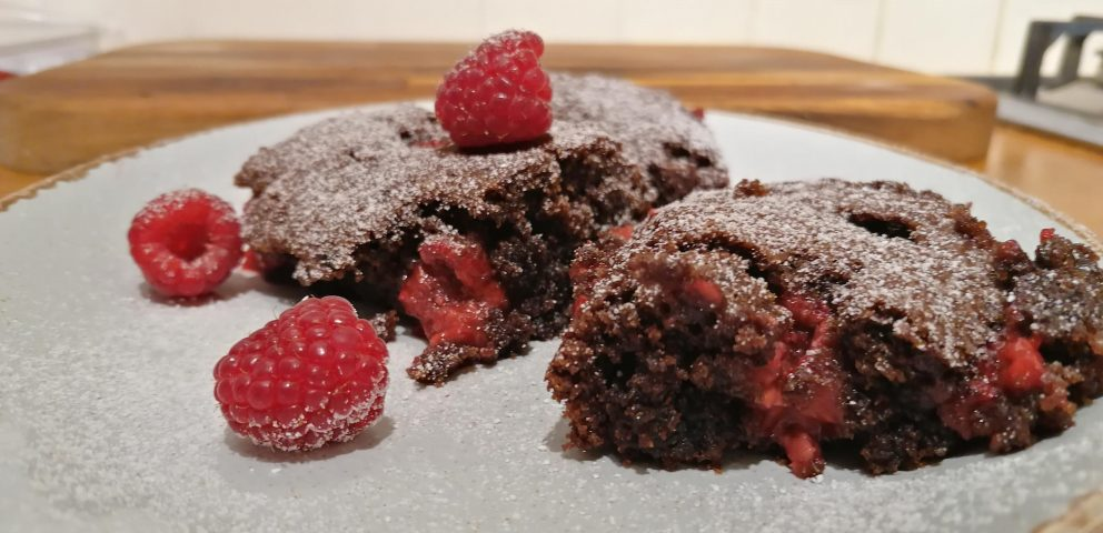 A plate of fresh, warmed and gooey vegan chocolate brownies with fresh raspberries scattered on top