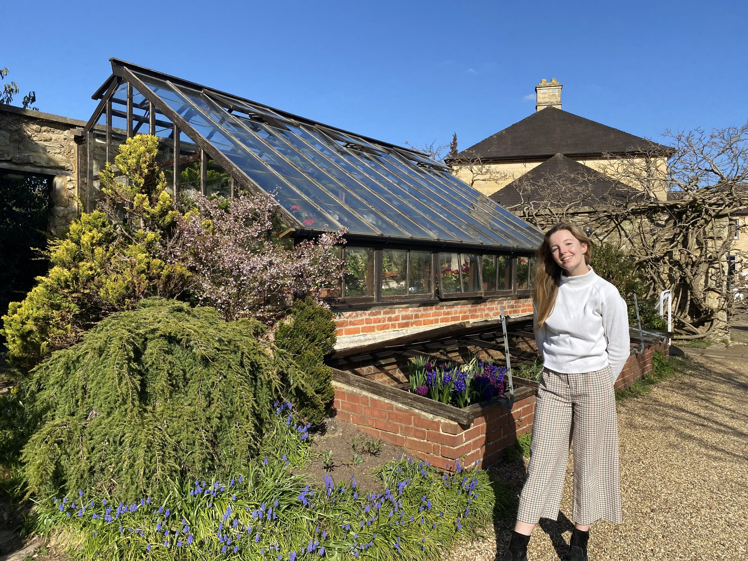 Clinical medicine student Ella Dunlop stands outside the Green Templeton greenhouse in the sunshine
