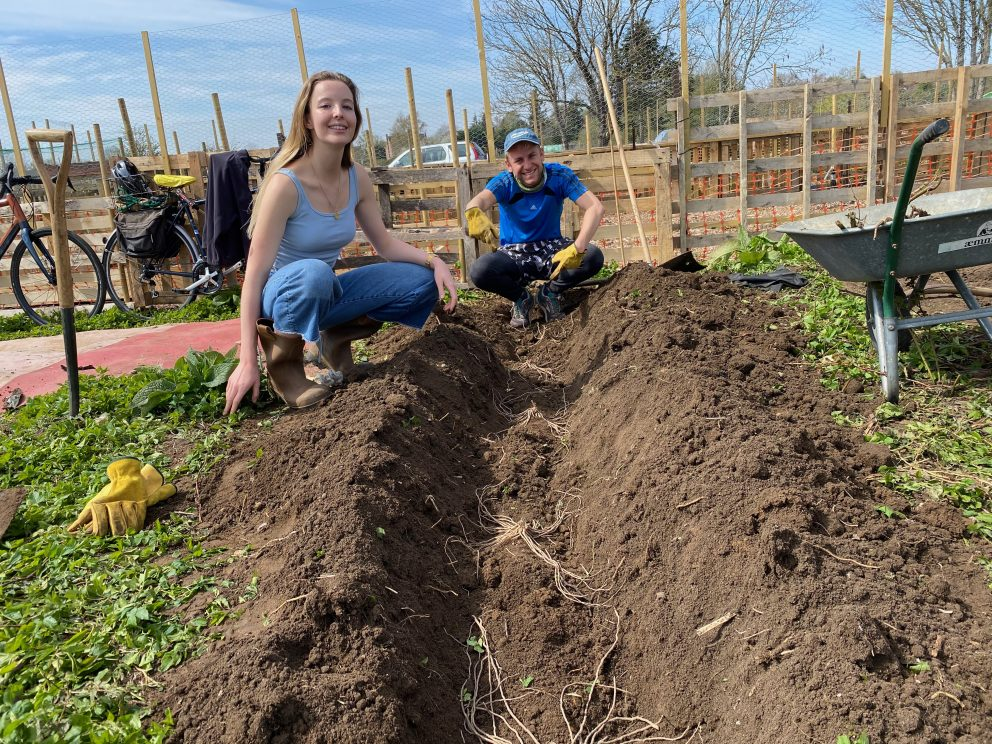 Two allotment team members pose next to a freshly dug bed ahead of planting raspberries