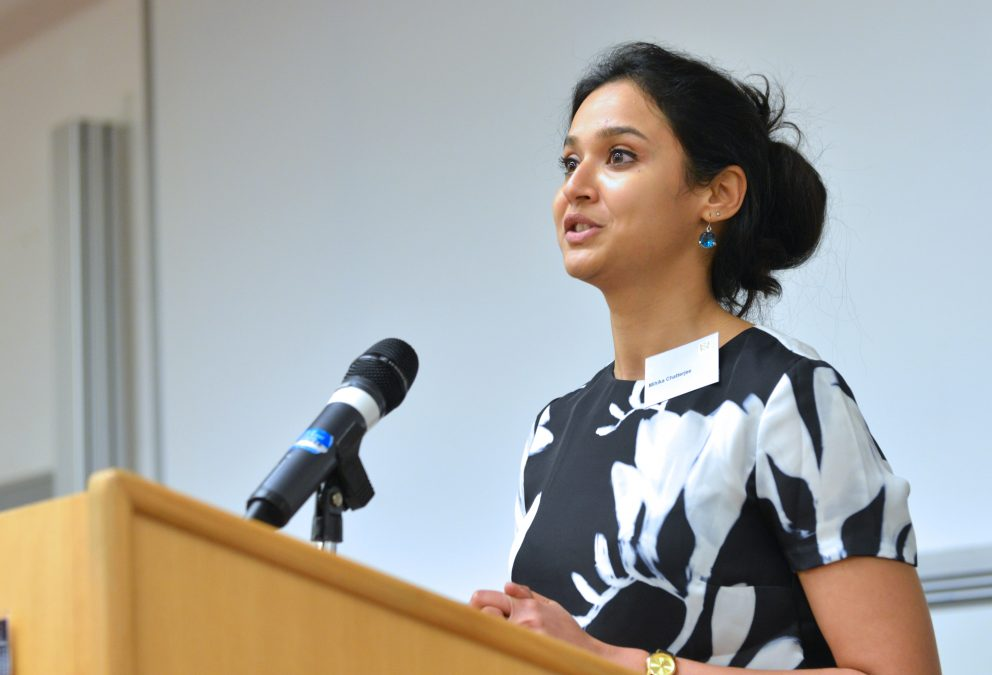 Mihika Chatterjee speaks at a wooden podium during an Emerging Markets Symposium