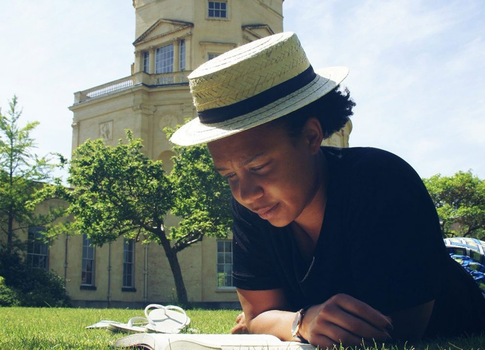 A student reads a book in the sunshine while lying on the grass outside the Radcliffe Observatory