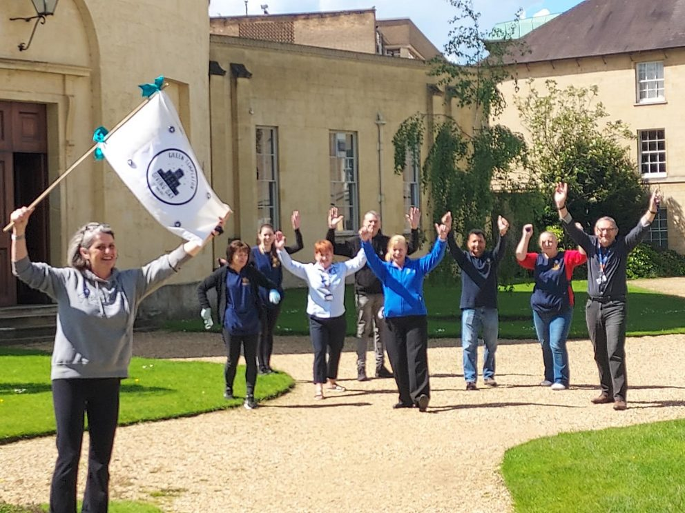 Staff members throw their hands in the air outside the Radcliffe Observatory