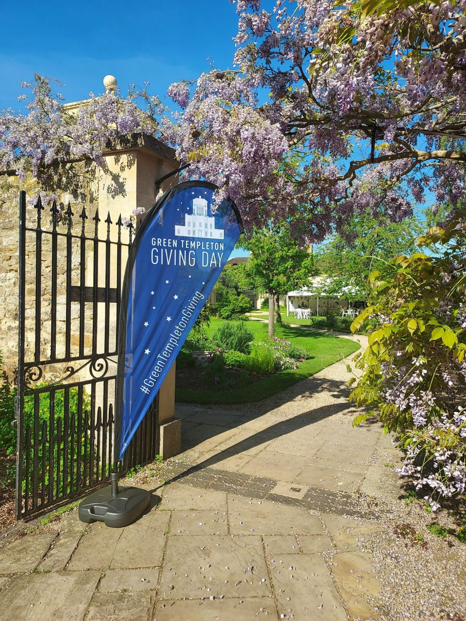 A blue flag with the words 'Green Templeton Giving Day' flies on a gate outside the Radcliffe Observatory