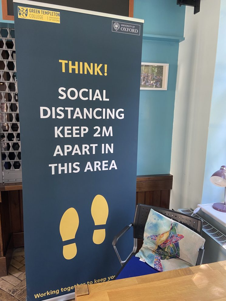 A banner reading 'Think! Social Distancing. Keep 2m apart in this area'