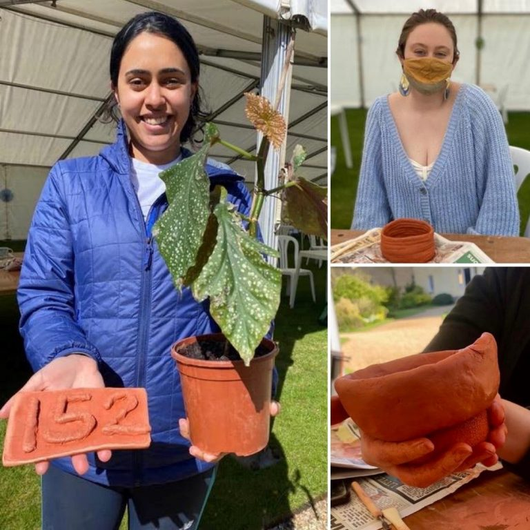 Students holding pots and number made from clay at GCR-led pottery event