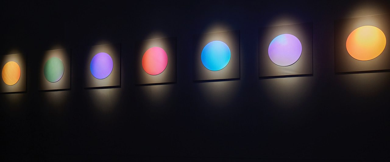 An 8m row of discs created using vivid Pure Structural Colour mounted on a wall
