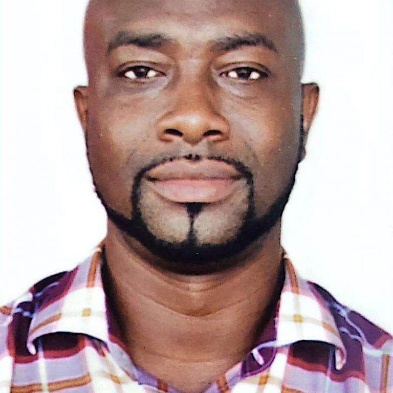 Makafui Tunde Adebayo, facing the camera directly wearing a checked shirt